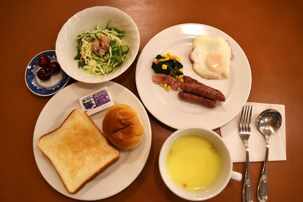 洋食 (パン・コーンスープ・サラダ・ウインナー・ほうれん草とベーコンの炒め物・目玉焼き・果物)